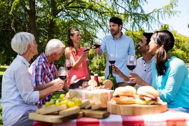 Família feliz tomando vinho tinto no parque