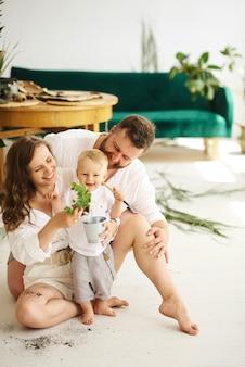 Família feliz trabalhando em casa. transplantar plantas com seu filho