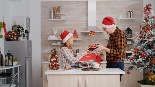 Família feliz trazendo embrulho de presente de natal com fita na cozinha decorada de natal