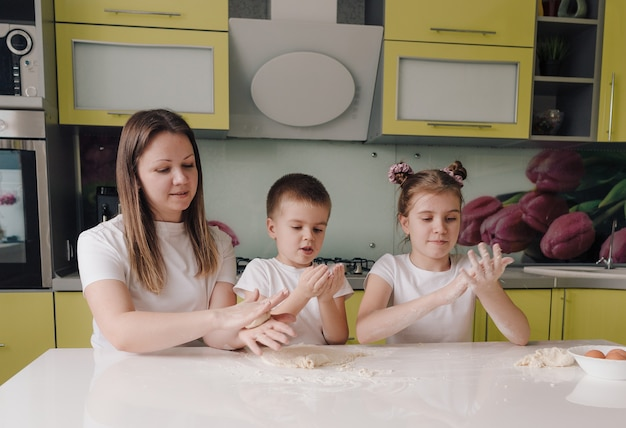 Família feliz, uma mãe e dois filhos pequenos aprendem a fazer massa na cozinha de uma casa