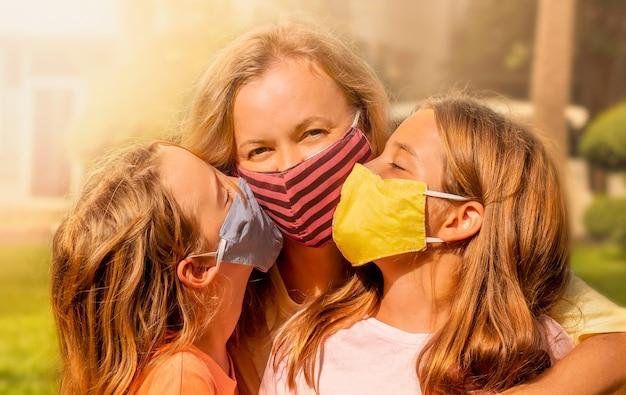 Família feliz usando as máscaras faciais. meninas mascaradas beijam mãe feliz.