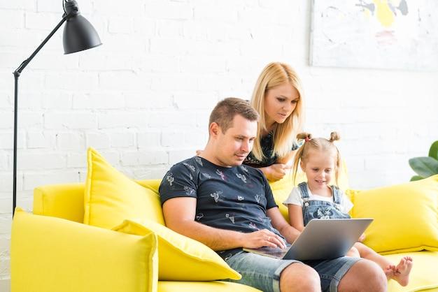 Família feliz usando o laptop em casa