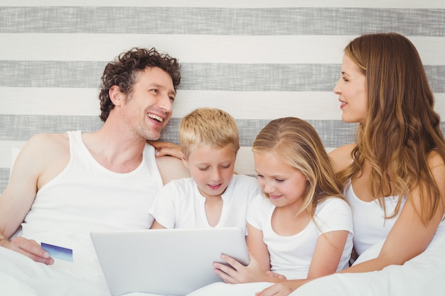 Família feliz usando o laptop na cama