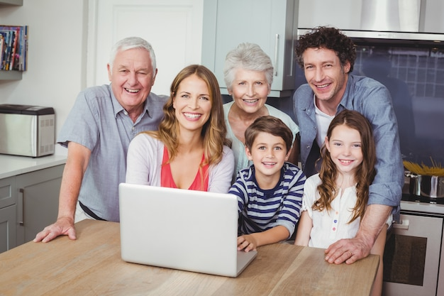Família feliz usando o laptop na cozinha