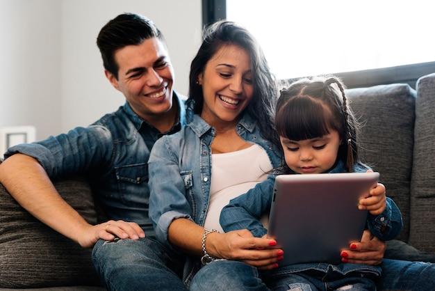 Família feliz usando o tablet em casa.