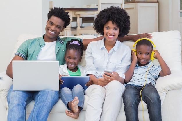 Família feliz usando tecnologias no sofá