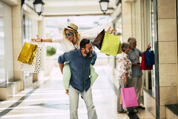 Família feliz vai às compras juntos - dois adultos se divertindo e dois idosos no bakcground olhando para as lojas - homem segurando uma mulher nas costas