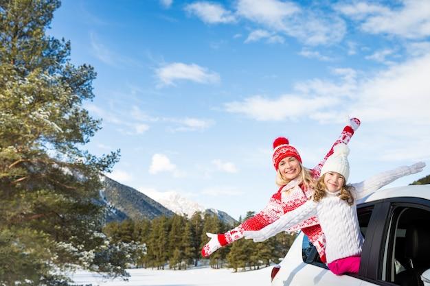 Família feliz viajando de carro pessoas se divertindo nas montanhas mãe e filho nas férias de inverno