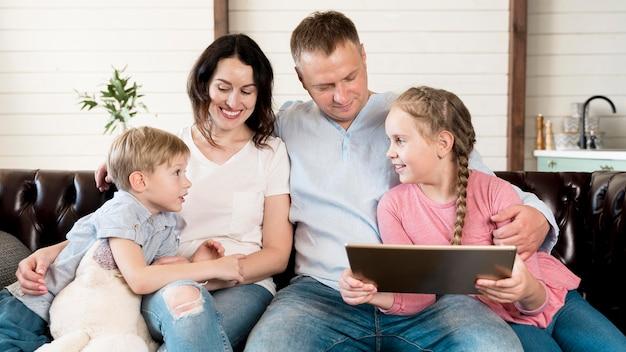 Família feliz vista frontal com dispositivo