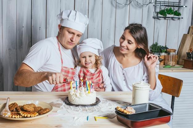 Família, filha feliz com mamãe e papai em casa na cozinha rindo e acendendo as velas do bolo de aniversário