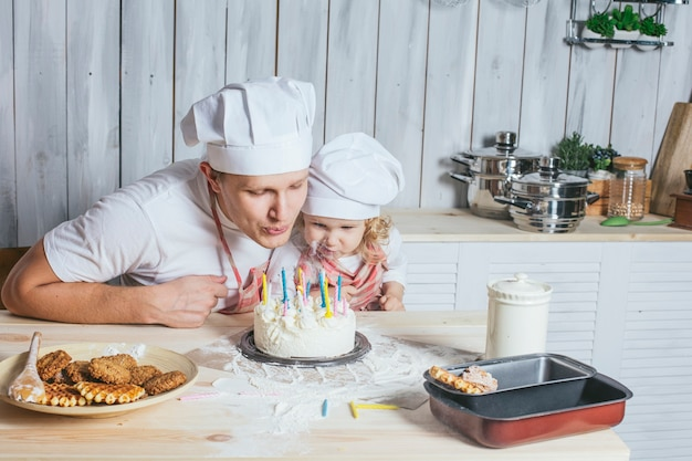 Família, filha feliz com meu pai em casa na cozinha ria e acendeu as velas do bolo de aniversário