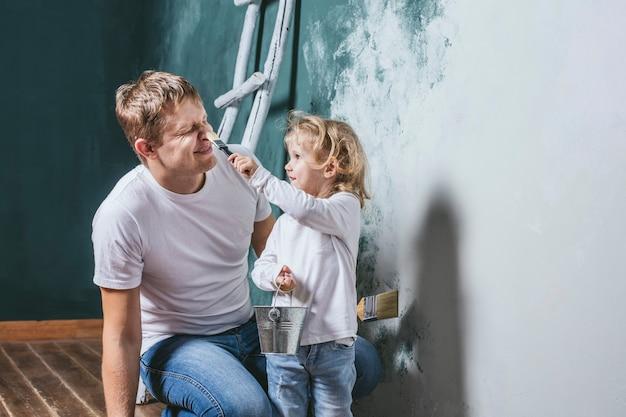 Família, filha feliz com pai fazendo reparos em casa, pintando paredes, junto com amor