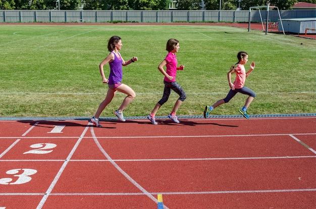 Família fitness, mãe e filhos correndo na pista do estádio, exercício com crianças e conceito de estilo de vida saudável do esporte