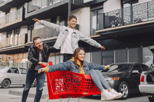 Família fofa brincando com um carrinho de compras em uma cidade