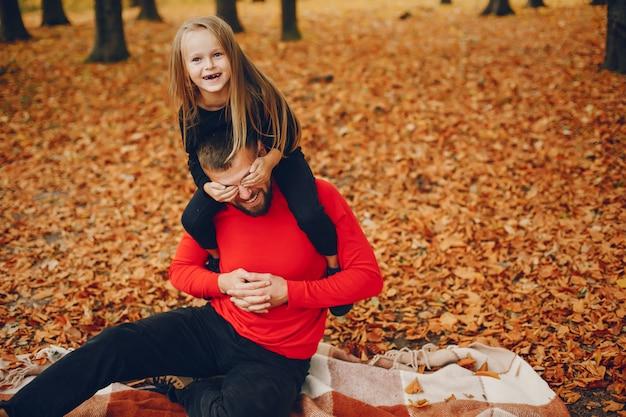 Família fofa brincando em um parque de outono