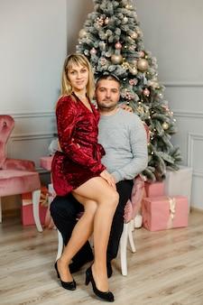 Família fofa comemora o natal. lindo casal perto da árvore de natal