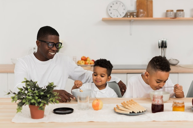 Família fofa comendo juntos na cozinha