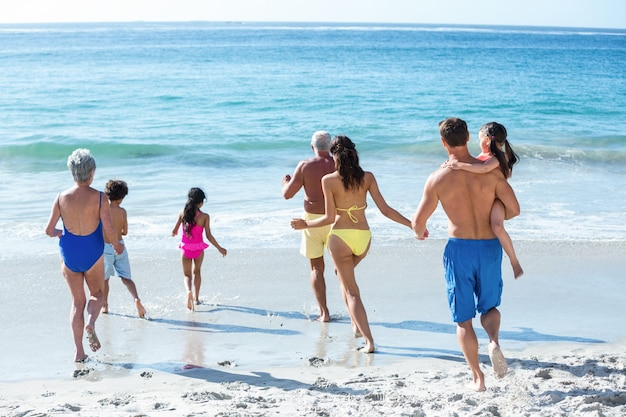 Família fofa de várias gerações correndo no mar