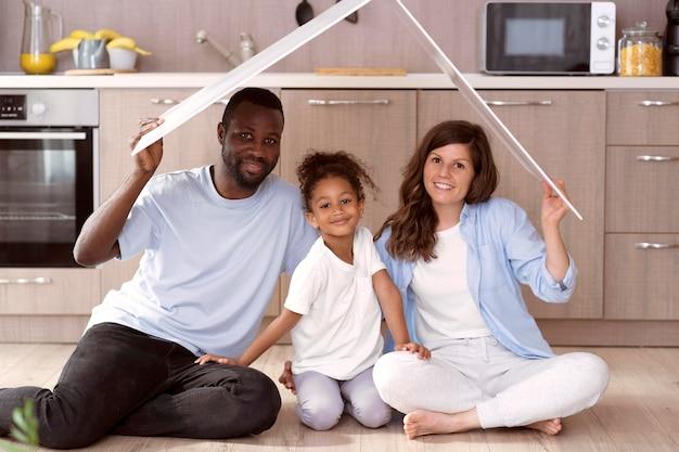 Família fofa segurando um telhado acima da cabeça