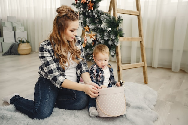 Família fofa sentado perto da árvore de natal