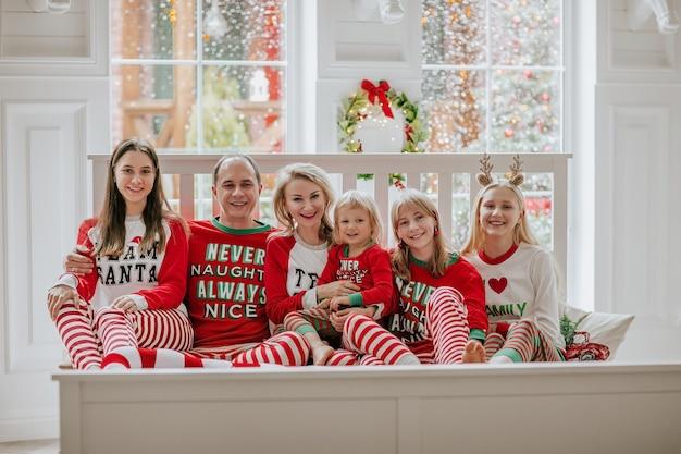 Família grande de seis pessoas com pijama de natal, sentados juntos na cama branca contra uma grande janela