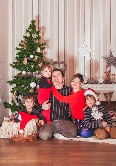 Família grande e alegre com chapéu de papai noel sentado no interior de uma casa decorada com natal