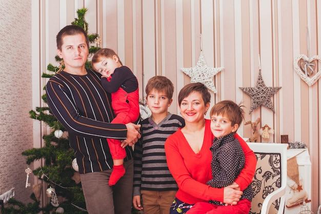 Família grande e alegre sentada no interior de uma casa decorada de natal