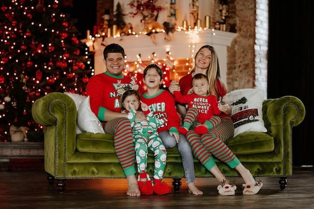 Família grande e jovem de cinco pessoas com pijama de natal, sentados juntos em um sofá contra cenário de natal.