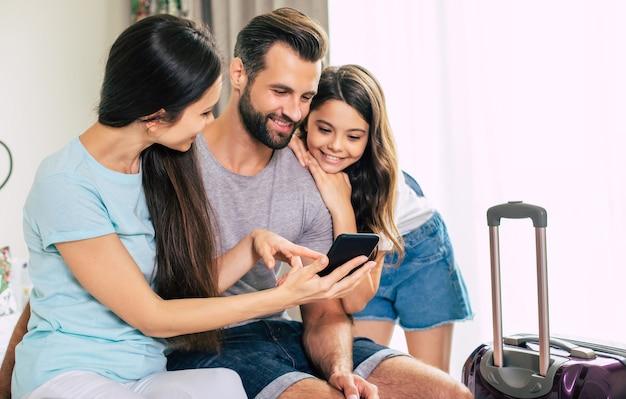 Família grande, feliz e animada, de turistas usando um smartphone enquanto estão sentados na cama no quarto do hotel
