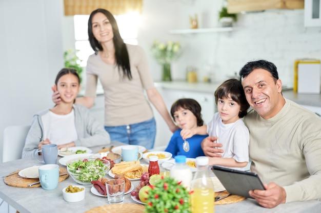 Família hispânica sorrindo para a câmera enquanto desfrutava de uma refeição juntos em casa. pai de meia-idade com filho usando o tablet pc, sentado à mesa da cozinha. paternidade, cozinha latina. foco seletivo