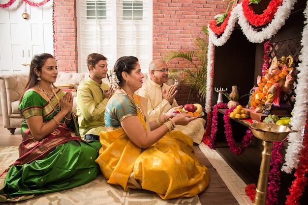Família indiana asiática inteligente realizando ganesh puja ou aarti em casa usando roupas tradicionais