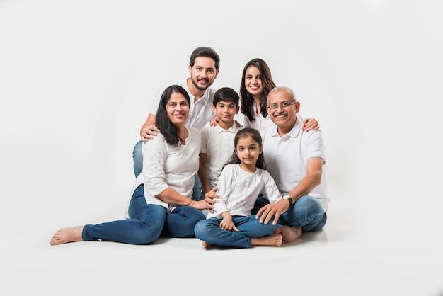 Família indiana asiática sentada sobre um fundo branco. casal sênior e jovem com filhos vestindo jeans e blusa branca. foco seletivo