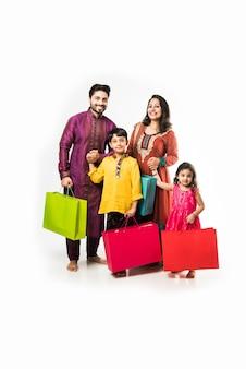 Família indiana celebrando diwali ou deepavali com roupas tradicionais com sacolas de compras, isolada sobre um fundo branco
