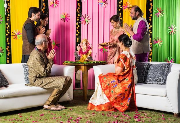 Família indiana celebrando ganesh chaturthi fazendo ganpati puja ou poojan