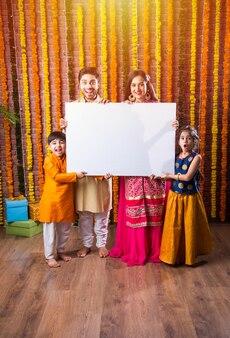 Família indiana celebrando o festival de diwali, segurando um quadro branco em branco ou um cartaz. em pé contra um fundo de decoração floral, olhando para a câmera