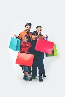 Família indiana com sacolas de compras no inverno e roupas quentes como pano de fundo