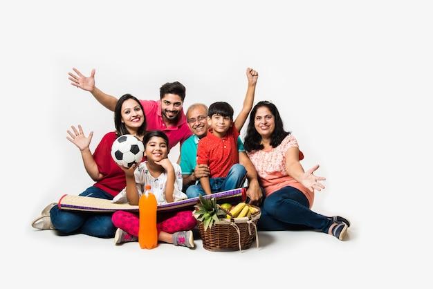 Família indiana desfrutando de piquenique dentro de casa - multi geração de família asiática sentada sobre um fundo branco com cesta de frutas, tapete, futebol e bebidas. foco seletivo