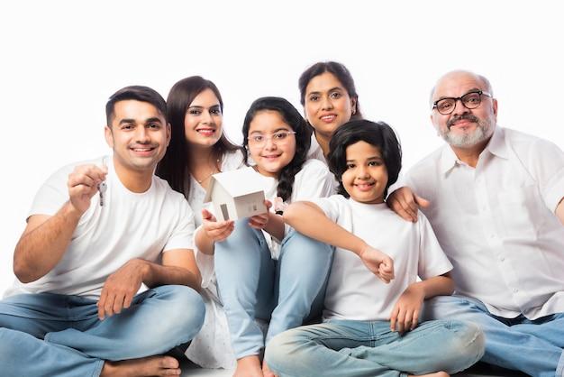 Família indiana e conceito imobiliário - família asiática multigeracional segurando um modelo de casa de papel com chaves contra um fundo branco
