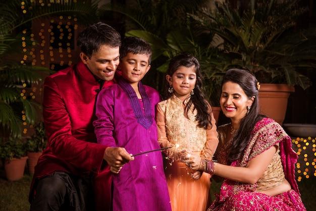 Família indiana em trajes tradicionais brincando com estrelinhas ou phuljhadi enquanto celebra o festival de diwali, ao ar livre