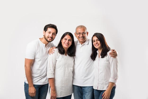 Família indiana feliz em pé isolada sobre fundo branco. pais idosos com filhos pequenos vestindo blusa branca e calça jeans azul. foco seletivo