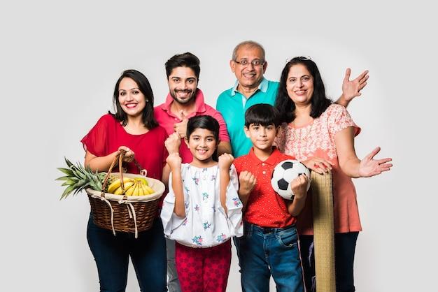 Família indiana indo para o piquenique - multi geração de família asiática em pé sobre um fundo branco com cesta de frutas, tapete, futebol e bebidas. foco seletivo