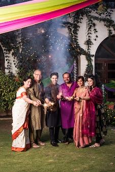 Família indiana multigeracional celebrando o festival de diwali brincando com fogos de artifício fora de casa