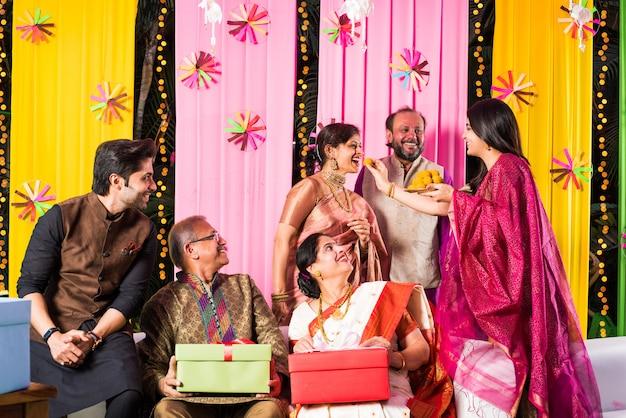 Família indiana multigeracional comendo doces enquanto celebra o festival ou ocasião vestida com roupas tradicionais, sentada no sofá ou sofá