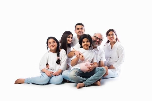 Família indiana multigeracional de seis pessoas segurando o cofrinho enquanto usa panos brancos e fica de pé contra uma parede branca