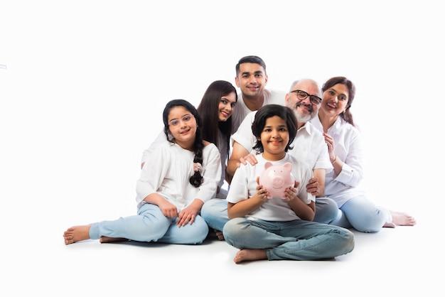Família indiana multigeracional de seis pessoas segurando o cofrinho enquanto usa panos brancos e fica de pé contra uma parede branca Foto Premium