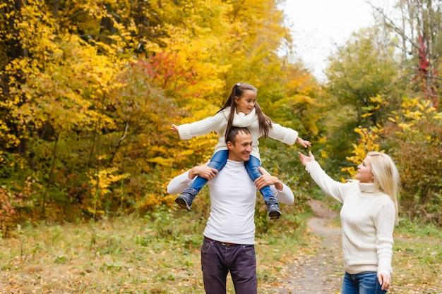 Família, infância, estação e conceito dos povos - família feliz no parque do outono