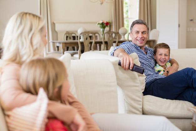 Família interagindo uns com os outros enquanto assiste tv na sala de estar