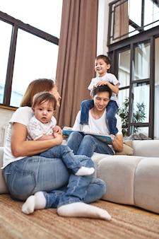 Família internacional em casa no sofá, abraçar e curtir a vida. vida familiar feliz.