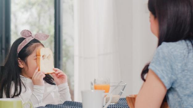 Família japonesa asiática toma café da manhã em casa. a filha asiática escolhe e joga o sorriso de riso do pão com os pais ao comer flocos de milho cereal e leite na bacia na tabela na cozinha moderna de manhã.