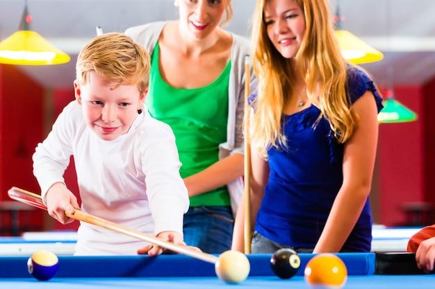 Família jogando bilhar juntos, o irmão começa com fila e bolas na mesa de bilhar